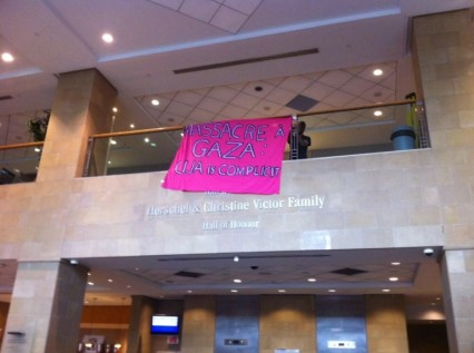"Image description: Photo of the lobby of the Federation CJA building in Montreal. Over the banner of the second floor, a banger hangs reading ""Massacre à Gaza: CIJA is Complicit. CIJA (Centre for Israel-Jewish Affairs) offices are located on the second floor near the banner."